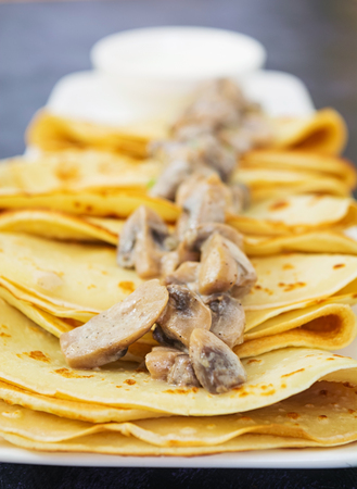 Pancakes with mushrooms on white background
