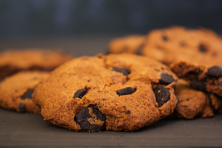 Cookies with chocolate on dark wooden background