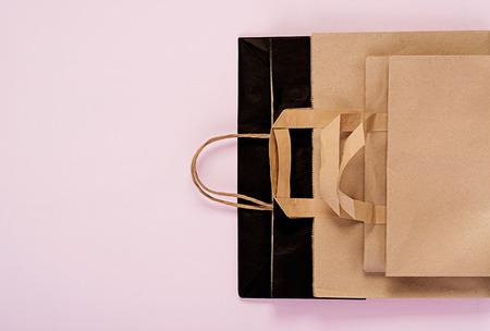 Diferentes bolsas de papel reciclable sobre fondo rosa. Concepto de reciclaje ecológico. Vista superior