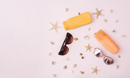 Sunglasses with sunscreen cream, defferent seashell and starfish on pink background. Top view. Flat lay Reklamní fotografie