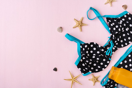 Swimsuit with different seashells and starfish on pink background. Top view Zdjęcie Seryjne