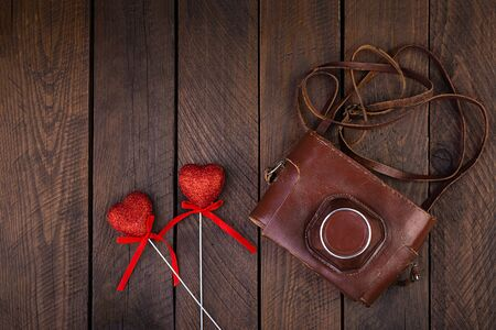 Vintage old camera with hearts on rustic wooden background. Top view Stock Photo