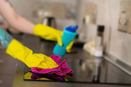 Woman in protective gloves wiping dust using cleaning spray and duster. Cleaning service concept.