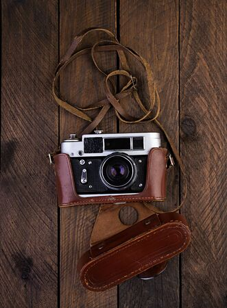 Vintage old camera on rustic wooden background. Top view