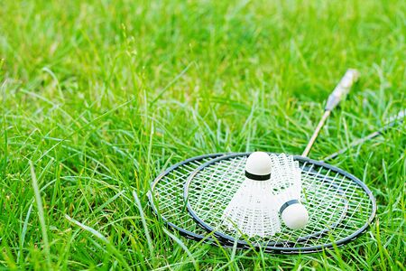 Shuttlecock and badminton rackets on a green lawn