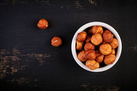 Hazelnuts on dark wooden background. A handful of nuts.