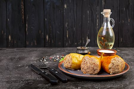 Colorful stuffed peppers with rice and minced meat on wooden background. Imagens