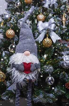 New Year background. Gnome with heart in hands on background of decorated Christmas tree.