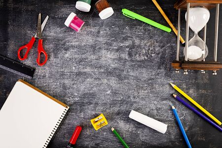 Background of dirty chalkboard. School concept with stationery supplies.