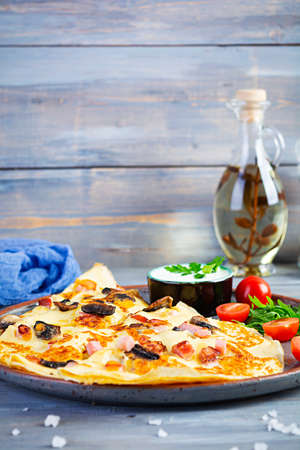 Delicious pancakes with mushrooms, ham and cheese, arugula, tomatoes and sour cream on a wooden background