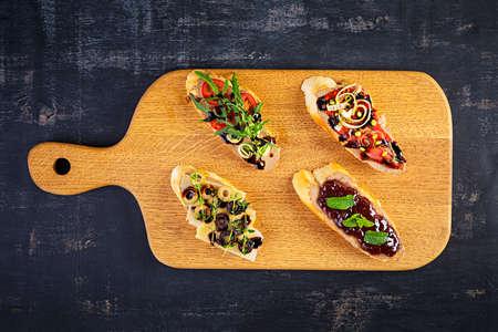 Bruschetta with chicken liver paste. Delicious bruschettas with various fillings. Different bruschetta ob wooden background Foto de archivo