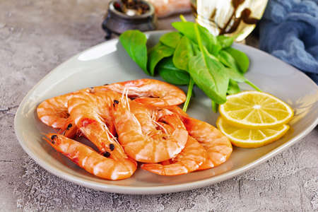 Delicious cooked shrimps in plate isolated on gray background. Boiled prawns
