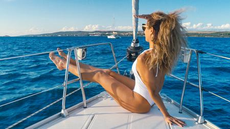 Meisje in een bikini rust op een jacht in het midden van de oceaan. Mooi meisje in het resort. Weekend op een jacht. Cruise op een jacht op zee.