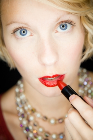 Lady with amazing eyes putting lipstick (like in front of a mirror) photo