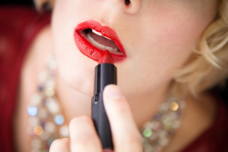 Lady putting lipstick - closeup photo