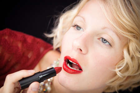 Lady putting lipstick photo
