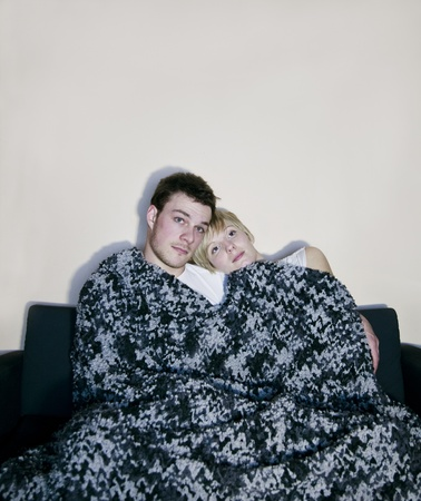 Young couple watching television comfortably wrapped in a blanket  photo