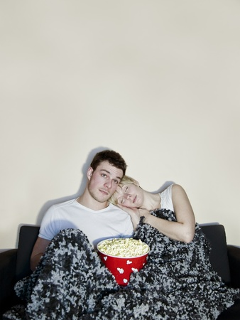 Young couple watching television and eating a huge bowl of fresh buttered popcorn comfortably wrapped in a blanket  The movie might be a bit boring since both of then are sleeping    in the popcorn     photo