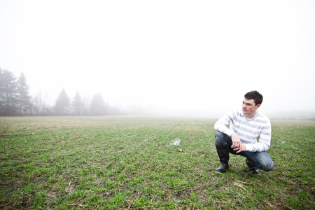 to crouch: In the foggy field Stock Photo
