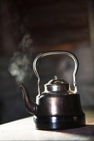 Boiling silver kettle on a wood stove photo