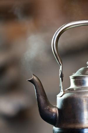 tea kettle: Boiling silver kettle on a wood stove