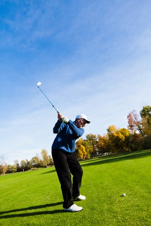 Man playing golf on a beautiful day photo