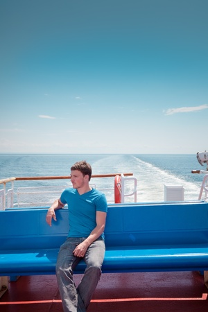 yachtsman: The young man on the deck against the sea Stock Photo