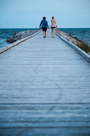 littoral: Two girls walking on the pier