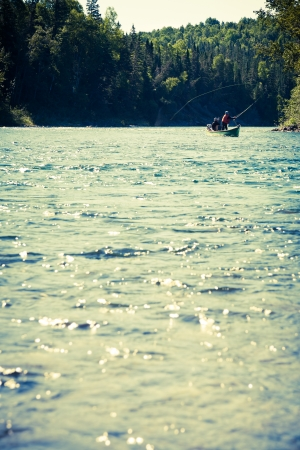 Fishermen fly fishing the salmon on a jolly-boat photo