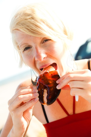 person appetizer: Girl eats lobster claw outdoor on a dinning table with sunlight