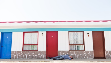 Motel and a man lying near the door 免版税图像
