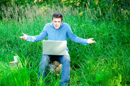 confused person: incomprehension of a man lost in nature with technology