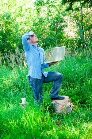 despaired: Despaired Young man outdoors with a cup and laptop