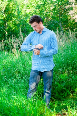Young man in nature adjusting cufflinks and getting ready