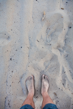 man legs: Mens feet in the sand Stock Photo