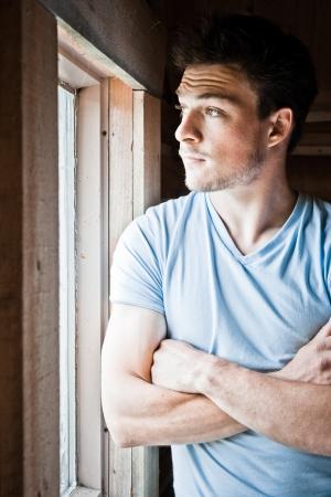 Young man at the window Фото со стока