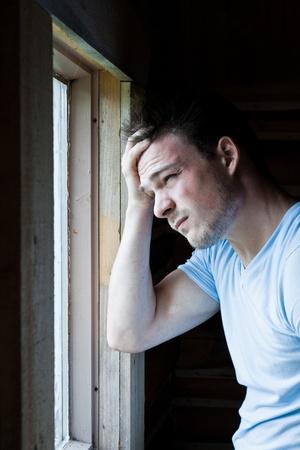 persona deprimida: Hombre joven en la ventana