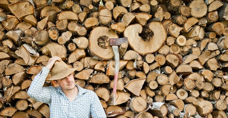 energy work: Woodcutter with straw hat on a background of wood taking a break Stock Photo