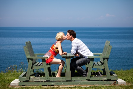 kissing lips: Romantic couple kissing on the bench in vacation Stock Photo