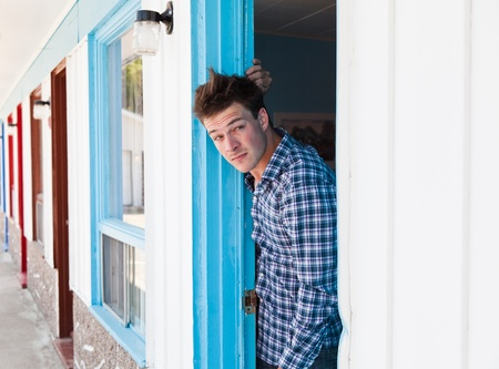 Worried young man looks out of the ugly motel room photo