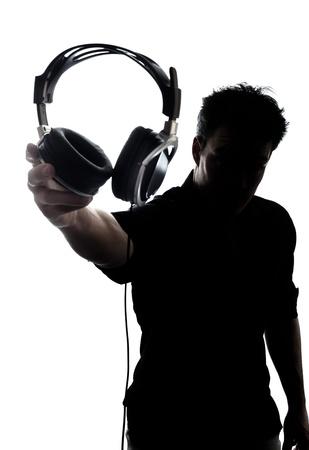 oir: Hombre en silueta mostrando auriculares aislados en fondo blanco Foto de archivo