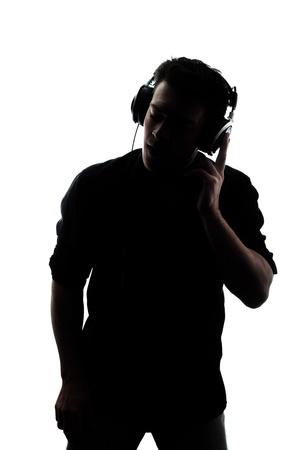 auriculares dj: Mujer en silueta escucha a los auriculares aislados en el fondo blanco Foto de archivo