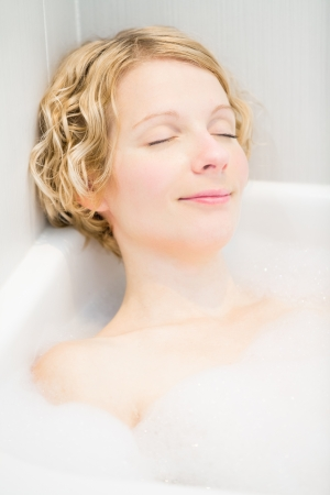 woman in bath: Happy young woman relaxing in the bath