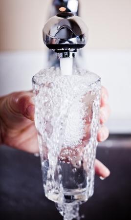 vaso con agua: Hombre sediento llenar un vaso rebosante de agua