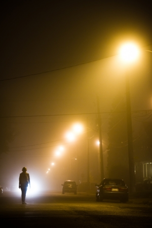 scared girl: Woman alone in the middle of the foggy street