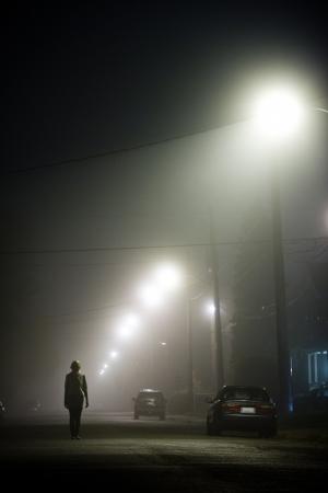 alone: Mujer sola en el medio de la calle de niebla