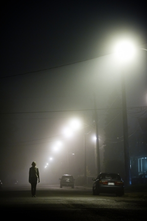 girl alone: Woman alone in the middle of the foggy street