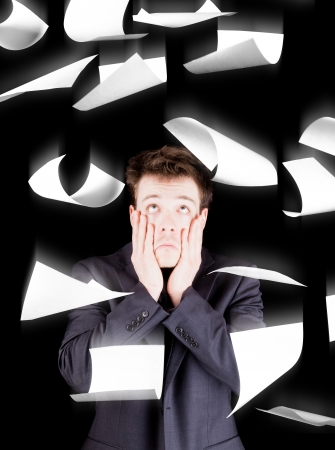 despaired: Despaired businessman with paperwork falling everywhere isolated on black background Stock Photo
