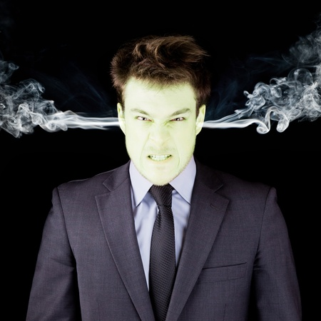 Furious businessman getting green isolated on black Stock Photo