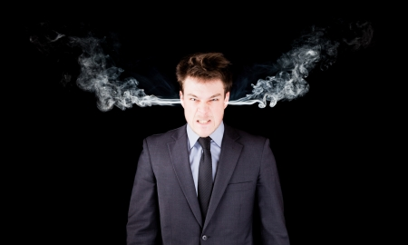 Portrait of a furious businessman isolated on black